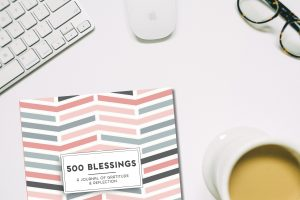 picture of desktop and coffee, keyboard, and reading glasses along with 500 Blessings: A Journal of Gratitude & Reflection by Perky Bird Journals with Pink and Grey Chevron Cover