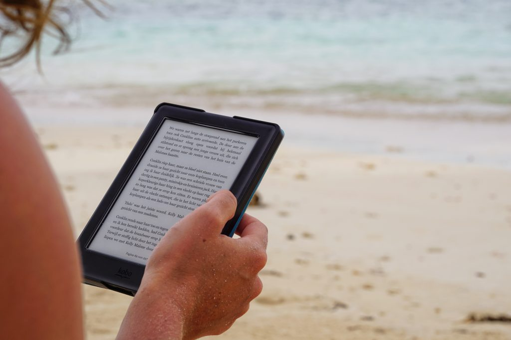 woman at beach reading book on e-reader